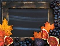 Πλαίσιο φθινοπώρου με τον πίνακα κιμωλίας, τα φύλλα, τα σύκα και το σταφύλι, διαστημικά FO Στοκ εικόνες με δικαίωμα ελεύθερης χρήσης