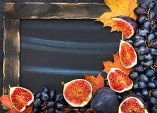 Πλαίσιο φθινοπώρου με τον πίνακα κιμωλίας, τα φύλλα, τα σύκα και το σταφύλι, διαστημικά FO Στοκ Φωτογραφία