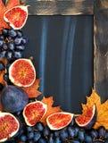 Πλαίσιο φθινοπώρου με τον πίνακα κιμωλίας, τα φύλλα, τα σύκα και το σταφύλι, διαστημικά FO Στοκ φωτογραφία με δικαίωμα ελεύθερης χρήσης