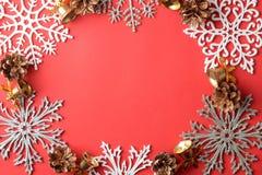 πλαίσιο φιαγμένο από snowflakes και ντεκόρ Χριστουγέννων σε ένα κόκκινο υπόβαθρο επάνω από την όψη στοκ φωτογραφίες
