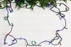 Πλαίσιο Χριστουγέννων των φω'των γιρλαντών στους κλάδους έλατου μοντέρνο borde Στοκ Εικόνα