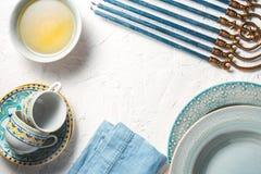 Πλαίσιο Chanukiah, βούτυρο σε ένα κύπελλο, πιάτα και φλυτζάνια Στοκ Φωτογραφίες