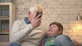 πλαισιωμένος εγγονός παππούδων βιβλίων καναπές η ανάγνωση φωτογραφιών οριζόντια ακούσματός του που κάθεται Ο ηληκιωμένος κρατά έν απόθεμα βίντεο