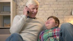 πλαισιωμένος εγγονός παππούδων βιβλίων καναπές η ανάγνωση φωτογραφιών οριζόντια ακούσματός του που κάθεται Ο ηληκιωμένος κρατά έν φιλμ μικρού μήκους