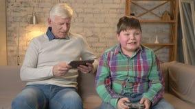 πλαισιωμένος εγγονός παππούδων βιβλίων καναπές η ανάγνωση φωτογραφιών οριζόντια ακούσματός του που κάθεται Ένας ηληκιωμένος χρησι απόθεμα βίντεο