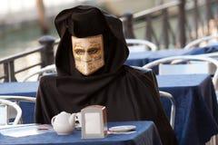 Πλαστή μάσκα που έχει το πρόγευμα στη Βενετία κατά τη διάρκεια του καρναβαλιού Στοκ Φωτογραφίες