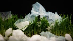 Πλαστικά απορρίμματα που εμφανίζονται στη χλόη από κάτω από το λειώνοντας χιόνι, οικολογία timelapse απόθεμα βίντεο