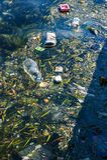 Πλαστικά συντρίμμια και ένα επιπλέον σώμα παπουτσιών στη θάλασσα στοκ φωτογραφία