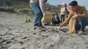 Πλαστικά φλυτζάνια και άχυρα στην παραλία και την ομάδα καθαρισμού εθελοντών απόθεμα βίντεο