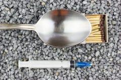 Πλαστική σύριγγα, ένα κουτάλι και μια αντιστοιχία στο λεπτό αμμοχάλικο στοκ φωτογραφία με δικαίωμα ελεύθερης χρήσης