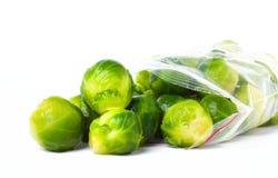 Πλαστική τσάντα με τις παγωμένες Βρυξέλλες - νεαροί βλαστοί που απομονώνονται στο λευκό veget Στοκ Φωτογραφία