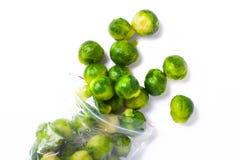 Πλαστική τσάντα με τις παγωμένες Βρυξέλλες - νεαροί βλαστοί που απομονώνονται στο λευκό veget Στοκ Εικόνες