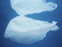 Πλαστική τσάντα που επιπλέει στο νερό Μολυσμένος περιβαλλοντικός Ανακυκλώστε στοκ εικόνα