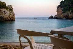 Πλαστικοί έδρες και πίνακας που αντιμετωπίζουν τον ωκεανό Μακρινός πυροβολισμός μιας μικρής βάρκας σε μέση και δύο απότομους βράχ στοκ εικόνα