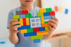 Πλαστικοί φραγμοί παιχνιδιών, σχεδιαστής των παιχνιδιών παιδιών ` s Φωτεινές δομικές μονάδες με μορφή μιας καρδιάς στα χέρια παιδ Στοκ Φωτογραφία