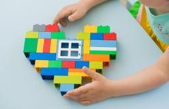 Πλαστικοί φραγμοί παιχνιδιών, σχεδιαστής των παιχνιδιών παιδιών ` s Φωτεινές δομικές μονάδες με μορφή μιας καρδιάς στα χέρια παιδ Στοκ εικόνα με δικαίωμα ελεύθερης χρήσης