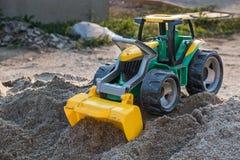 Πλαστικός μπροστινός φορτωτής παιχνιδιών στο σωρό άμμου στοκ φωτογραφίες