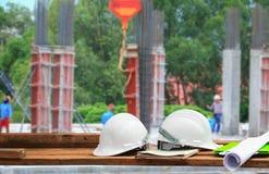 Πλαστικό και σχεδιάγραμμα κρανών ασφάλειας στο ξύλο με το υπόβαθρο εργασιακών χώρων εργοτάξιων κατασκευής θαμπάδων Στοκ Φωτογραφίες