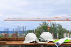 Πλαστικό και σχεδιάγραμμα κρανών ασφάλειας στο ξύλο με το υπόβαθρο εργασιακών χώρων εργοτάξιων κατασκευής θαμπάδων Στοκ φωτογραφία με δικαίωμα ελεύθερης χρήσης