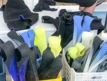 Πλαστικό κιβώτιο, καλάθι με τα πολύχρωμα λαστιχένια βατραχοπέδιλα κατάδυσης για την κολύμβηση, εξοπλισμός κατάδυσης σε ένα κιβώτι στοκ εικόνα