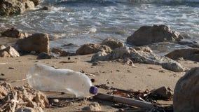Πλαστικό μπουκάλι στην αμμώδη παραλία με το ράντισμα κυμάτων Πλαστική έννοια ρύπανσης απορριμμάτων o απόθεμα βίντεο