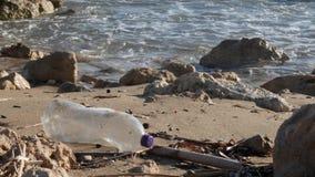 Πλαστικό μπουκάλι στην αμμώδη παραλία με το ράντισμα κυμάτων Πλαστική έννοια ρύπανσης απορριμμάτων απόθεμα βίντεο