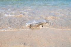 Πλαστικό μπουκάλι στην παραλία άμμου Στοκ Φωτογραφίες
