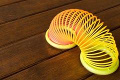 Πλαστικό ουράνιο τόξο παιχνιδιών σε έναν ξύλινο πίνακα Πολύχρωμη σπείρα για στοκ φωτογραφία με δικαίωμα ελεύθερης χρήσης
