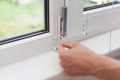 Πλαστικό παράθυρο επισκευών Handyman με hexagon Ο εργάτης ρυθμίζει τη λειτουργία του πλαστικού παραθύρου στοκ εικόνες