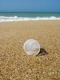 Πλαστικό φλυτζάνι απορριμάτων που βάζει στην άμμο στοκ εικόνα