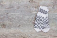 Πλεκτά άσπρα γάντια μαλλιού στο παλαιό ξύλινο υπόβαθρο με το διάστημα αντιγράφων στοκ φωτογραφία με δικαίωμα ελεύθερης χρήσης