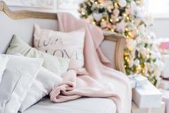 Πλεκτά καρό και μαξιλάρια σε έναν καναπέ στο σπίτι σε μια Παραμονή Χριστουγέννων Εγχώριο cosiness στοκ εικόνα