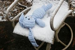 Πλεκτή άσπρη συνεδρίαση κουνελιών σε μια χιονισμένη καρέκλα Στοκ φωτογραφίες με δικαίωμα ελεύθερης χρήσης