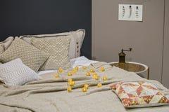 Πλεκτό κρεβάτι linens, πλεκτές μαξιλαροθήκες, μαξιλάρια, καλύμματα, γκρίζα μπεζ χρώματα, Σκανδιναβικό ύφος στοκ φωτογραφίες