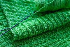 Πλεκτό πράσινο μαντίλι και πλέκοντας βελόνες Ανοικτό πράσινο μαντίλι clo Στοκ Φωτογραφία