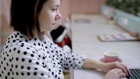 Πλευρά που βλασταίνεται μιας γυναίκας που εργάζεται στο lap-top στον καφέ, freelancer κάνοντας την εργασία της απόθεμα βίντεο