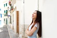 Πλευρά της όμορφης γυναίκας που στέκεται στην οδό που γελά με τα όπλα που διασχίζονται Στοκ Φωτογραφίες