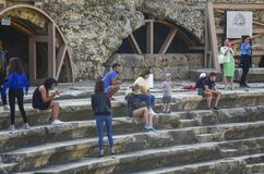 Πλευρά, Τουρκία - 19 Απριλίου - 2019: Μια ομάδα τουριστών που στηρίζονται και που παίρνουν τις εικόνες στα βήματα του αρχαίου αμφ στοκ εικόνα
