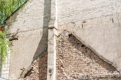 Πλευρά του νέου τοίχου προσόψεων κατοικημένου κτηρίου με την εναπομειναντίδα γραμμή παλαιάς γραμμής στεγών σπιτιών Στοκ εικόνα με δικαίωμα ελεύθερης χρήσης