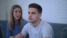 Πλευρικός παν πυροβολισμός του νέου ελκυστικού ζεύγους με τη λυπημένη ματαιωμένη και πιεσμένη στο σπίτι φίλη καναπέδων φίλων που  απόθεμα βίντεο