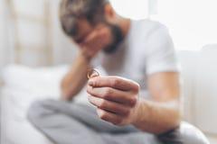 Πληγωμένο άτομο που κρατά ένα γαμήλιο δαχτυλίδι στοκ φωτογραφία