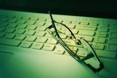 Πληκτρολόγιο lap-top, μολύβι και μαύρα γυαλιά χρυσή ιδιοκτησία βασικών πλήκτρων επιχειρησιακής έννοιας που φθάνει στον ουρανό Sel Στοκ Εικόνες