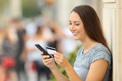 Πληρωμή κοριτσιών σε απευθείας σύνδεση με μια πιστωτική κάρτα και ένα τηλέφωνο Στοκ Εικόνα