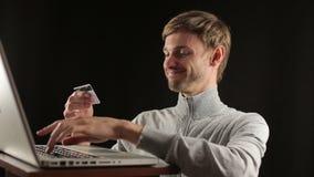 Πληρωμή που χρησιμοποιεί την πιστωτική κάρτα στο lap-top απόθεμα βίντεο