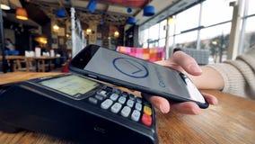 Πληρωμή Smartphone Το θηλυκό χέρι πληρώνει τη χρησιμοποίηση nfc του συστήματος και της ανέπαφης κάρτας απόθεμα βίντεο