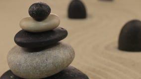 Πλησιάζοντας την πυραμίδα φιαγμένη από πέτρες και μαύρες πέτρες που στέκονται στην άμμο τρεκλίσματος απόθεμα βίντεο
