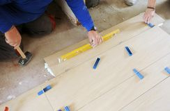 Πλινθοκτίστης που ελέγχει την ισοπέδωση ενός πατώματος κεραμικών πορσελάνης με το εργαλείο επιπέδων Στοκ φωτογραφία με δικαίωμα ελεύθερης χρήσης
