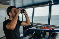 Πλοήγησης επιφυλακή ανώτερων υπαλλήλων στο ρολόι ναυσιπλοΐας που κοιτάζει μέσω των διοπτρών στοκ φωτογραφίες με δικαίωμα ελεύθερης χρήσης