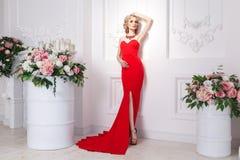 Πλουσιοπάροχα κυρία με το κόκκινο μακροχρόνιο φόρεμα, το κόσμημα και την ξανθή κυματιστή τρίχα, π στοκ εικόνες