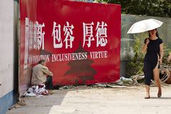 Πλούσια γυναίκα που περνά από έναν άστεγο στοκ φωτογραφία με δικαίωμα ελεύθερης χρήσης